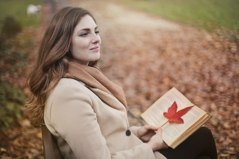 young woman with book in an autumn park sitting on a bench smiling