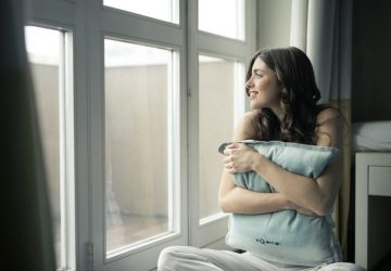 woman embracing a pillow looking outside the big windows