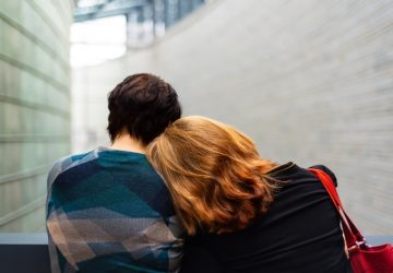 woman resting her head on another person's shoulder