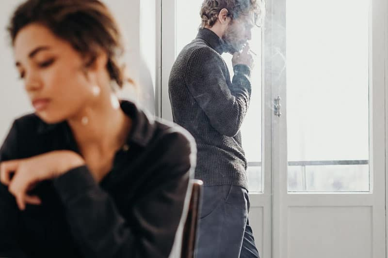 man standing while smoking near the window distant to a woman sitting