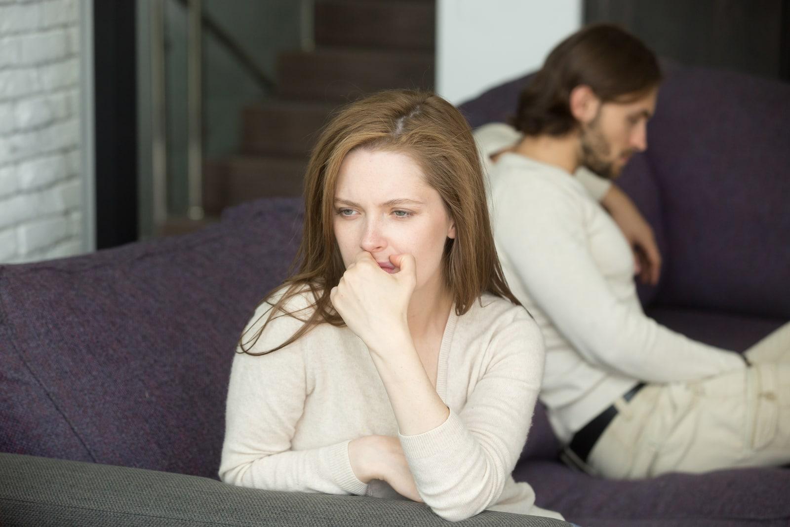 sad couple sitting on sofa