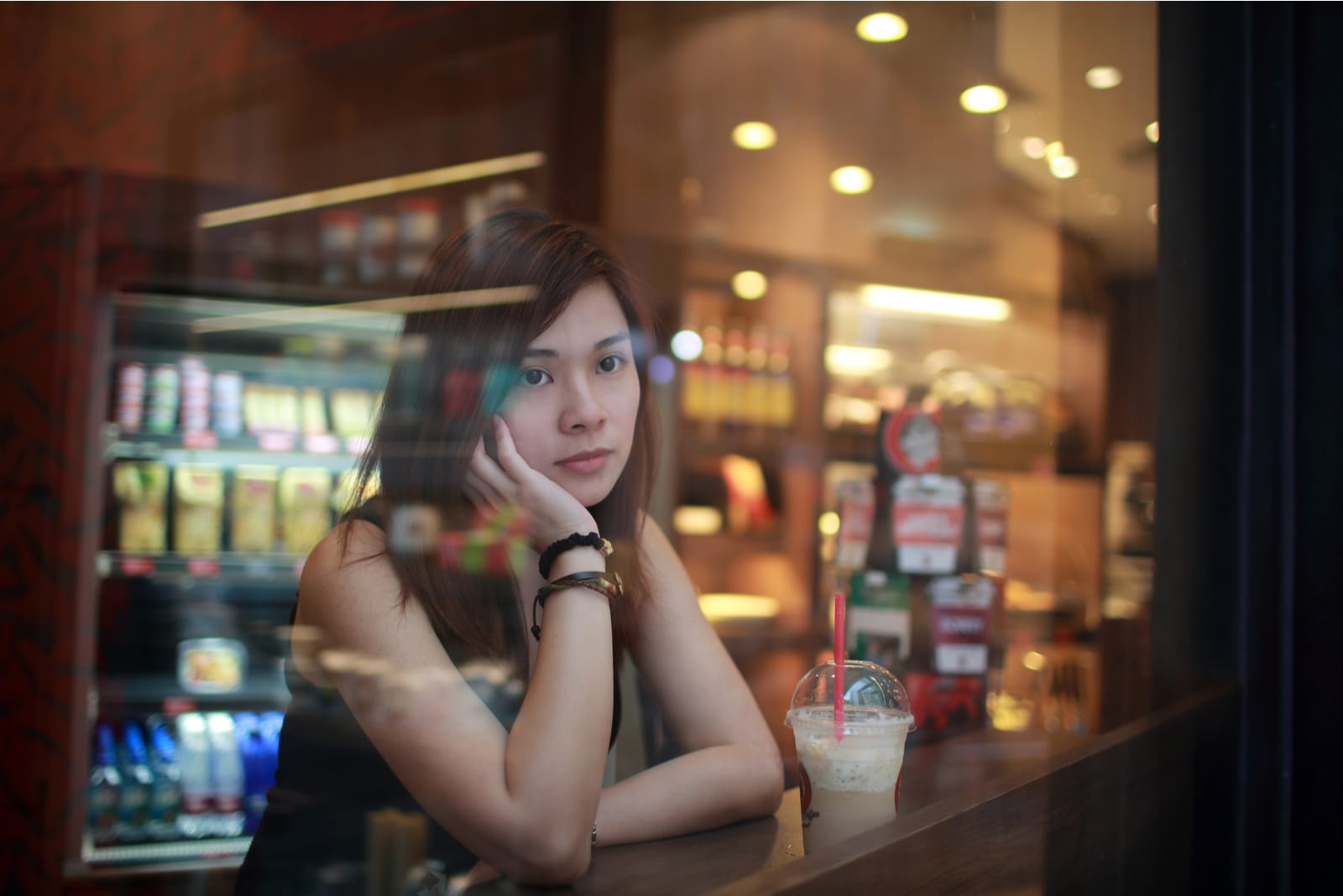 a sad Asian woman is sitting in a cafe behind the bar by the window