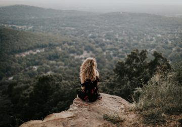 blonde woman sitting on cliff