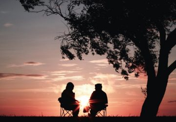 man and woman sitting on chairs during sunset