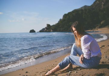 pensive woman sitting in the sand along the shore wearing white top and blue pants