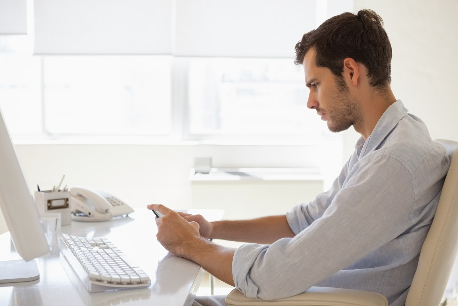Casual businessman sending a text at his desk in his office