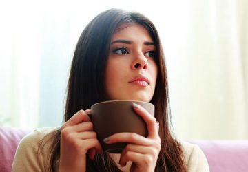 pensive woman sitting while holding a coffee cup