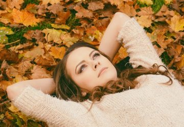 pensive young woman lying in the dried leaves during autumn season