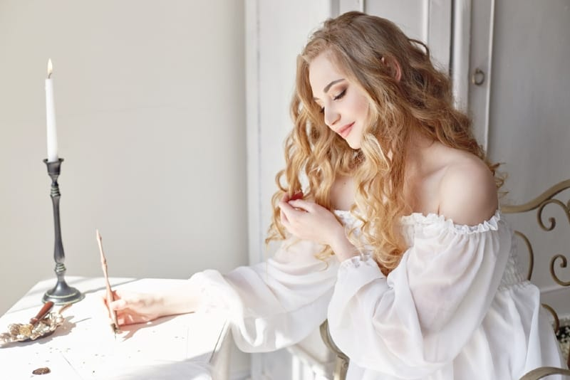 woman in white off-shoulder top writing letter at table