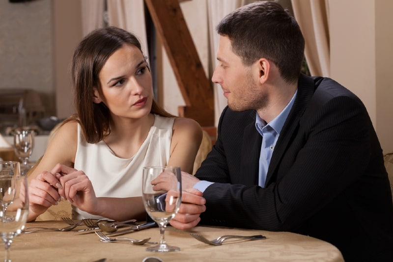 man and woman sitting at table waiting for dinner in restaurant
