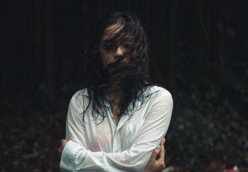 woman with face partly covered with wet hair wearing wet white long sleeved shirt