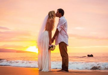 married couple kissing in the sunset in a beautiful beach of Hawaii