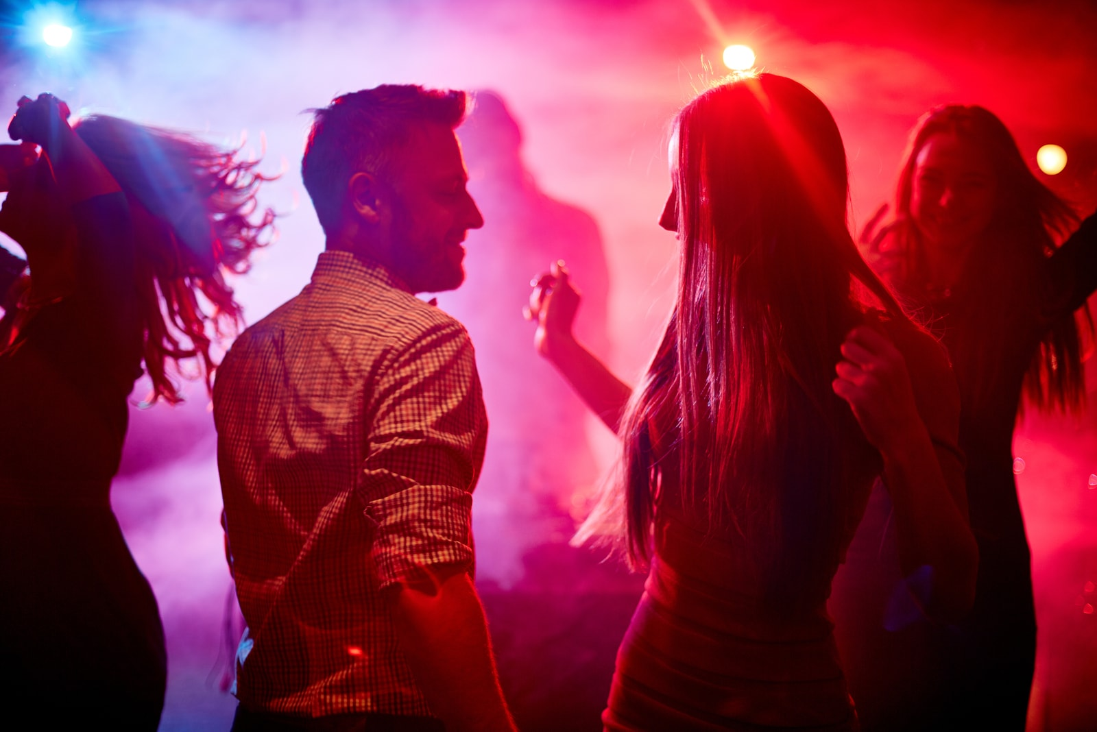 Happy couple and their friends dancing in disco club