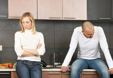 troubled couple not talking to each other inside the kitchen with man sitting on the sink near the woman
