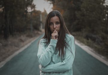 woman standing in the middle of the street biting her nails looking at the camera