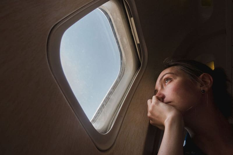 woman sitting near the window of an airplane looking outside