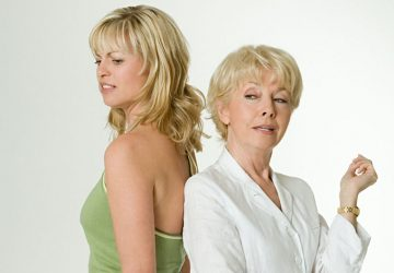 mother and daughter arguing standing back to back in white background