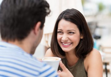 smiling woman holding cup of coffee looking at man
