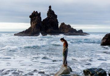 woman standing on rock near sea