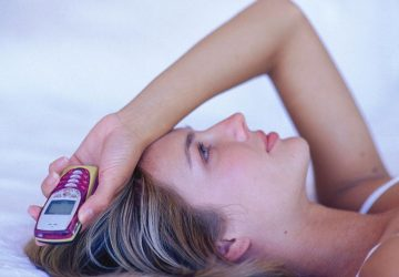 pensive woman holding an old analog cellphone in her hand while lying and hand on her head
