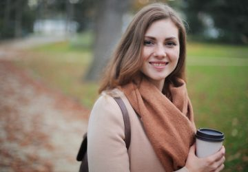 woman holding cup while smiling while outdoors