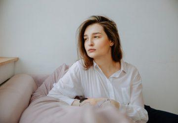 sad woman wearing white top sitting on the sofa