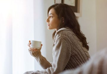thinking woman sitting and holding a cup of coffee