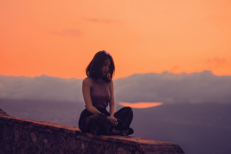 woman sitting on cliff during sunset