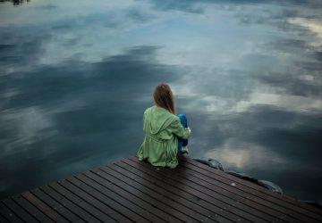 woman in green jacket sitting on wooden dock