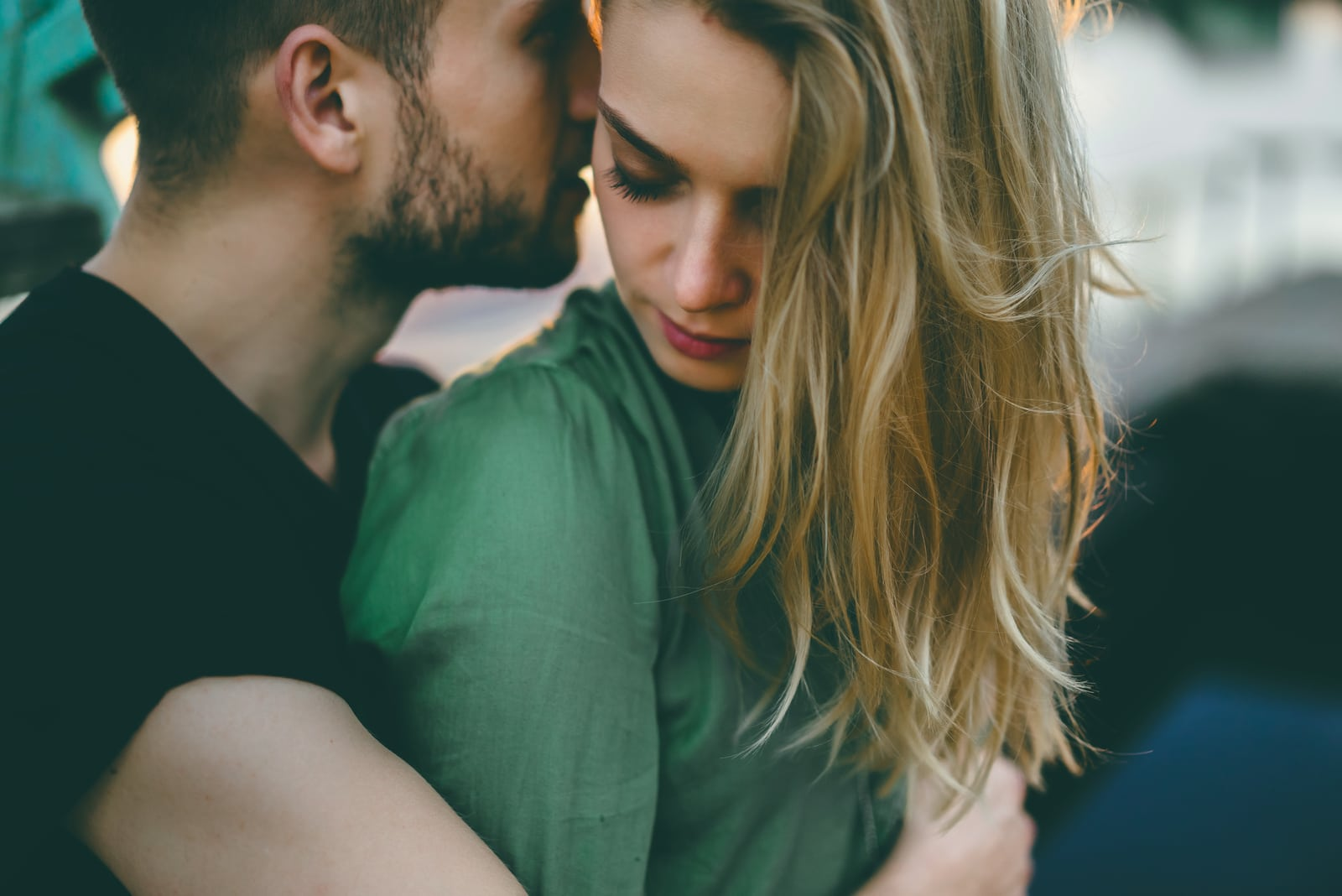 a bearded man hugs the blonde from behind