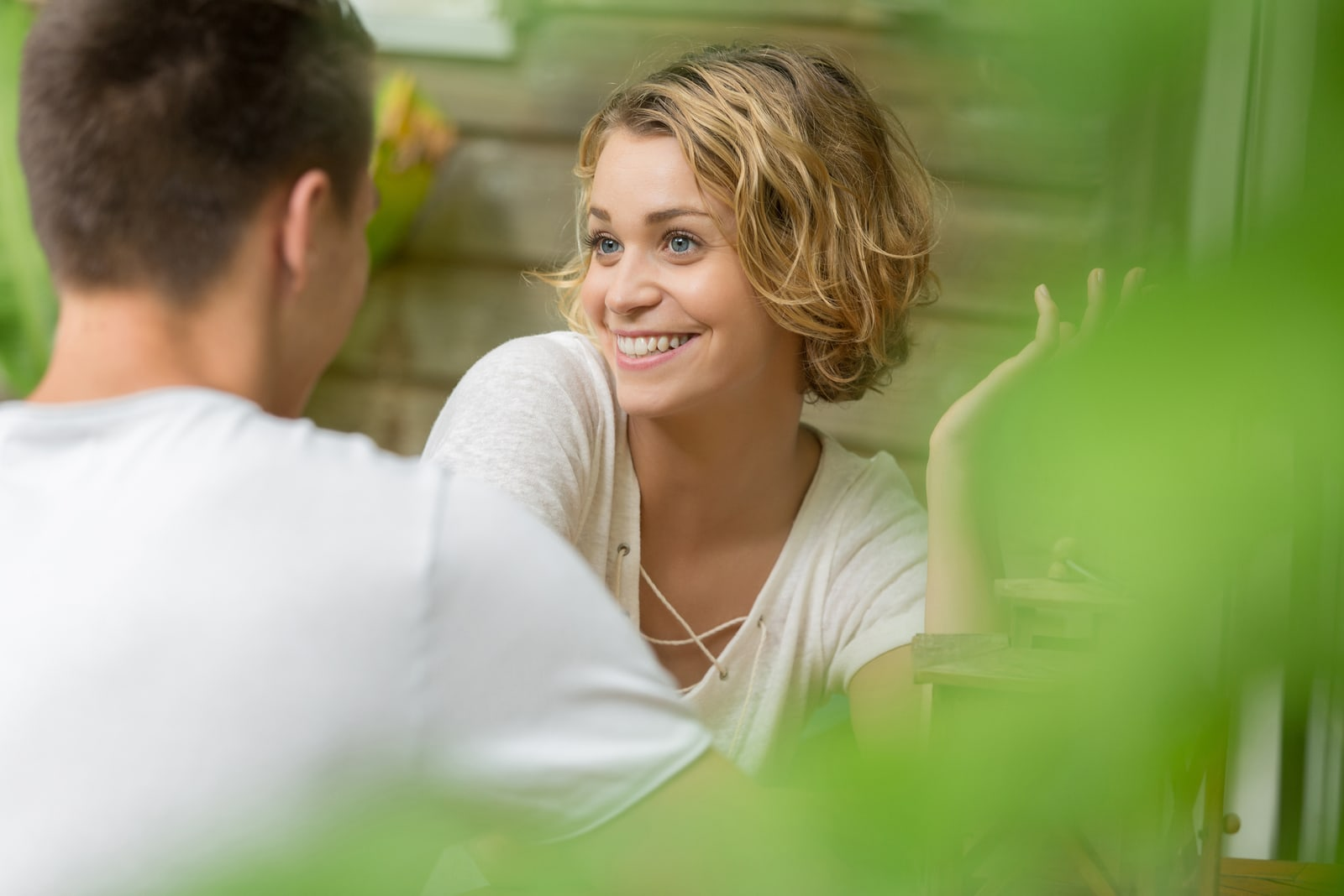 a beautiful smiling blonde sits with a man and they talk