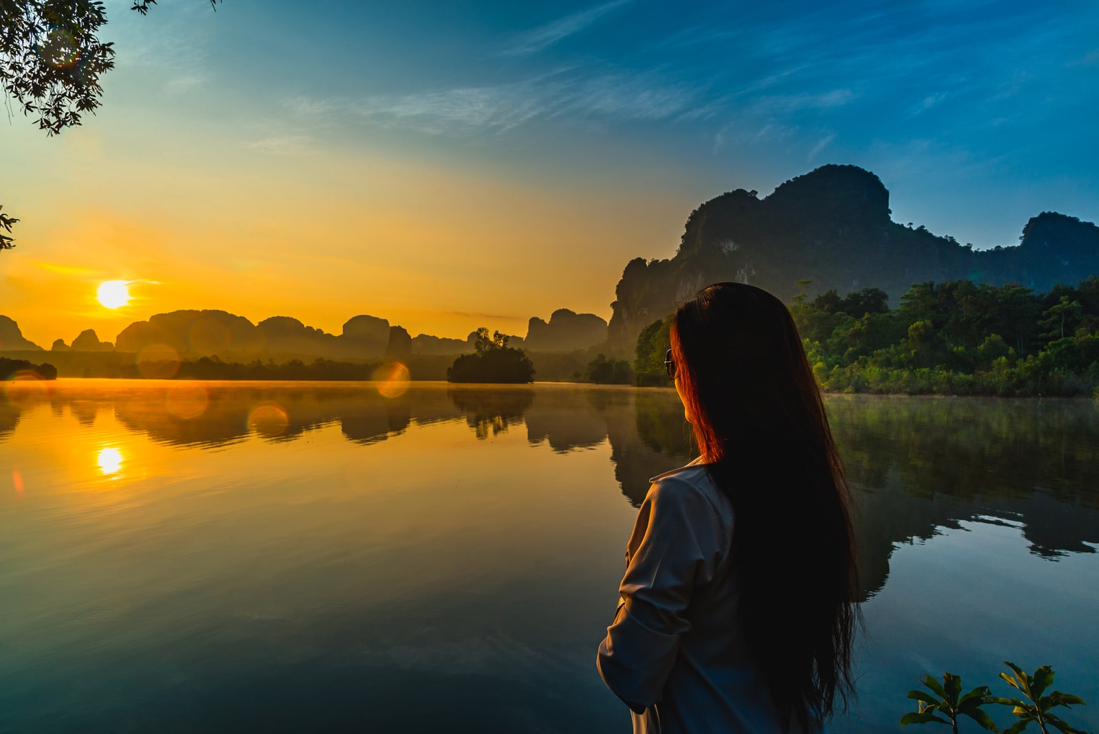 a beautiful woman stands by the lake and watches the sunset