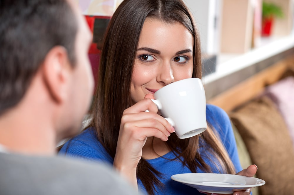 a man and a woman are sitting drinking coffee