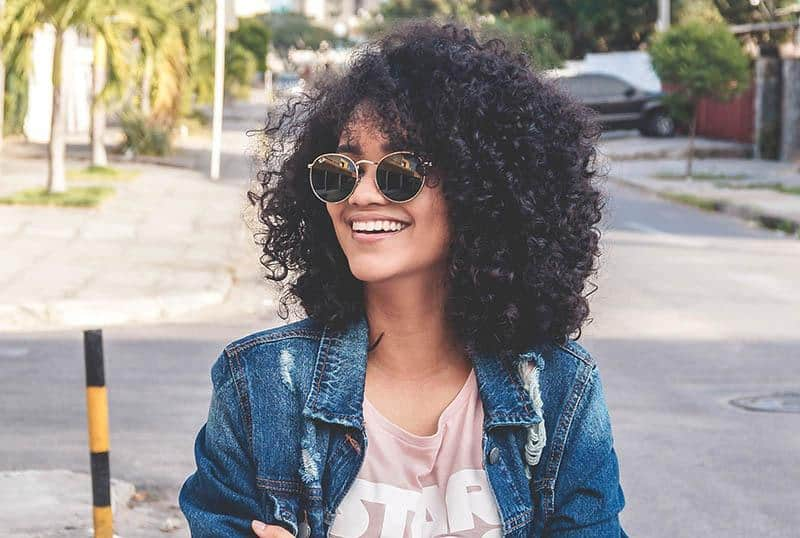 a portrait of a smiling black woman with sunglasses