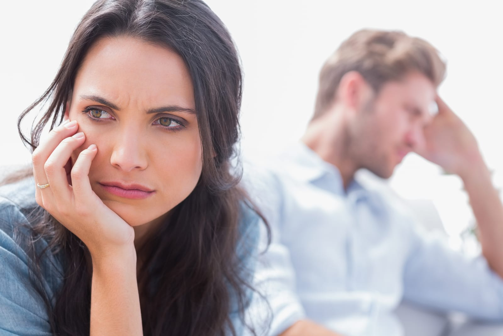 an angry brunette and a sad man sit after an argument