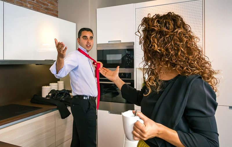 angry young businessman arguing with a woman carrying a cup
