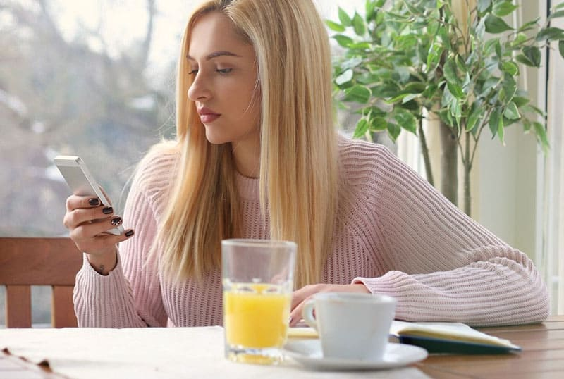 blonde woman texting while having breakfast with juice and tea on the table