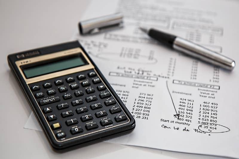 black calculator near pen on table