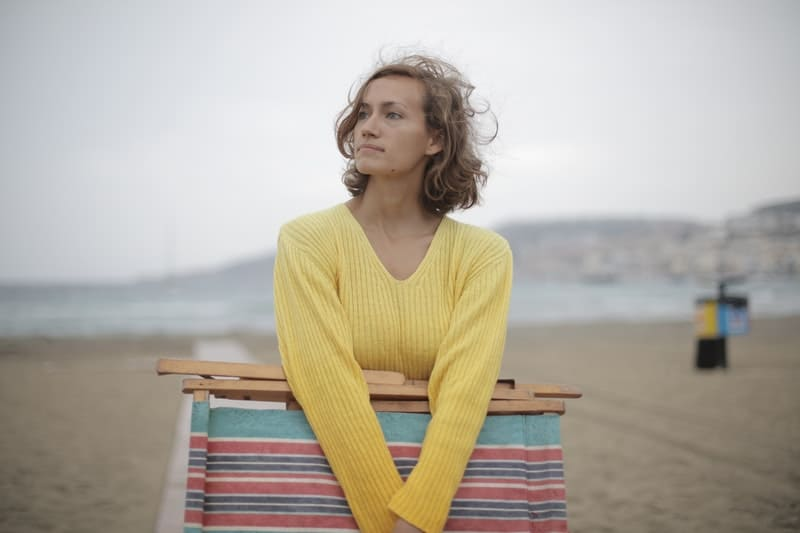calm female tourist with folded deck chair standing alone on a seashore in overcast weather