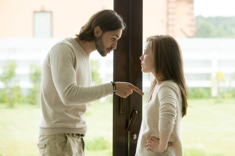 man and woman arguing while standing near door