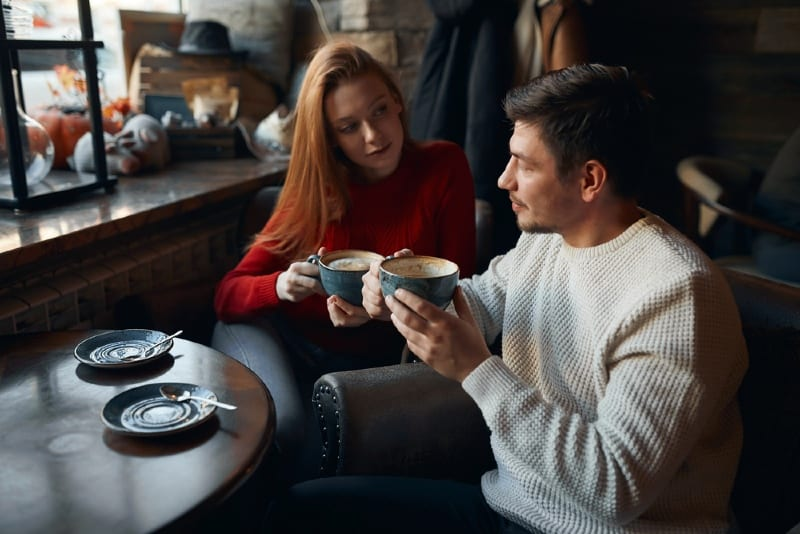 woman in red sweater and man having coffee while sitting at table