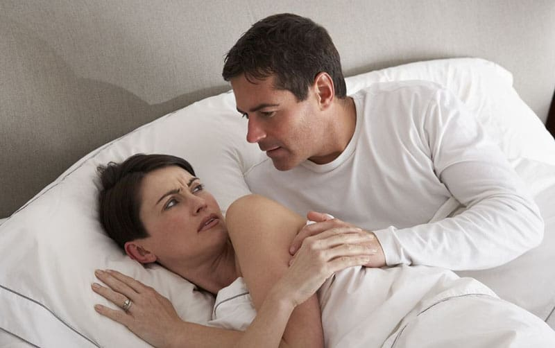 couple having disagreement in bed man trying to touch her