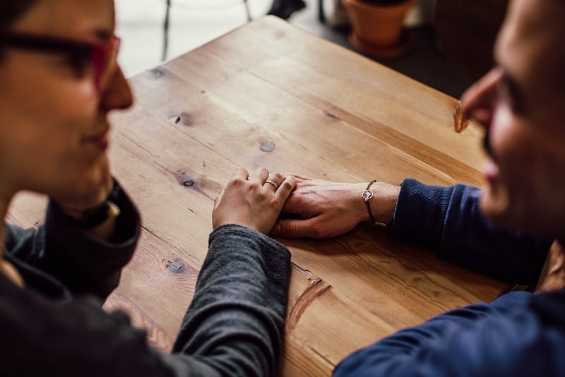 man and woman holding hands while sitting at table