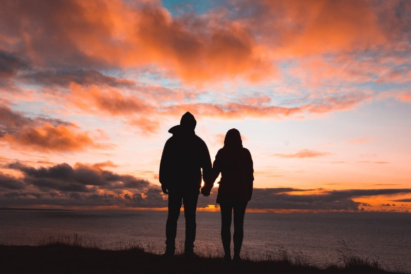 man and woman holding hands while standing on cliff during sunset