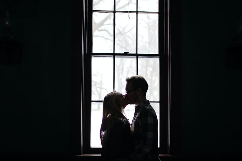 man and woman kissing while standing near window