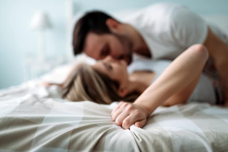 man in white t-shirt and woman kissing in bed