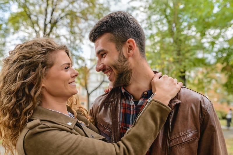 smiling man and woman making eye contact outdoor