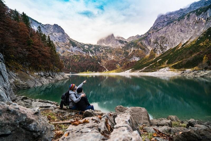 man and woman sitting near lake looking at mountain