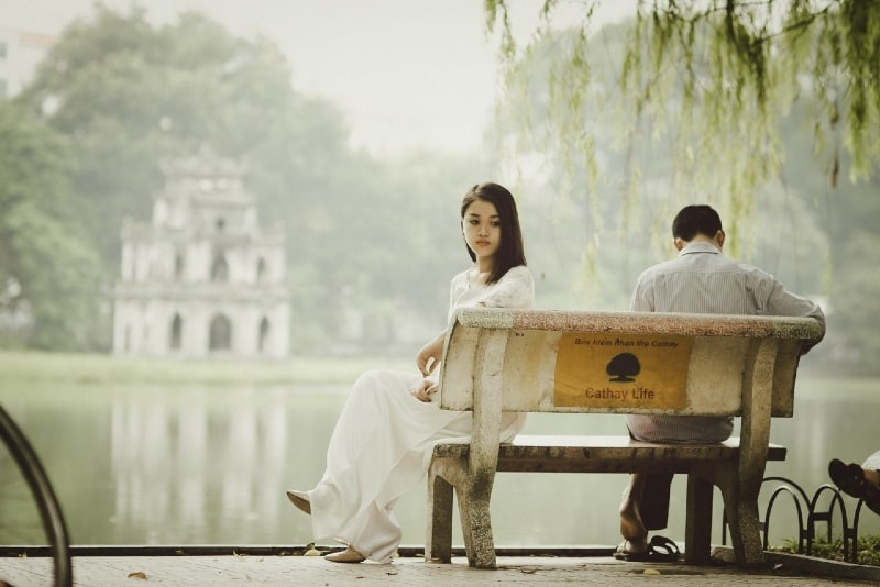 woman in white dress and man sitting on bench near water