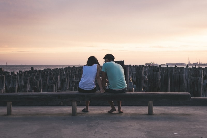 man and woman sitting on bench and talking